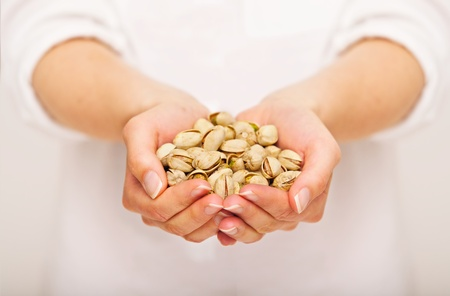 pistachios: Woman offering a handful of pistachio nuts