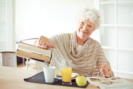 Happy senior woman having her breakfast at home looking at you photo