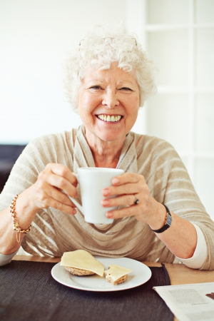 Smiling old lady having her breakfast at home photo
