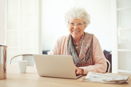 Cheerful senior woman using laptop as recreation at home photo