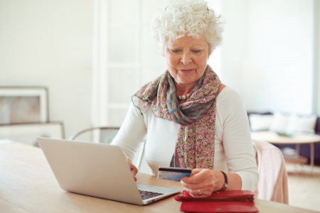 Grandmother in front of laptop paying online using a credit card photo