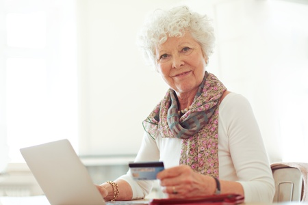 Smiling mature lady holding a credit card in front of her laptop photo