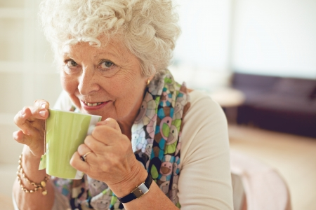 Closeup of a happy senior woman drinking tea photo