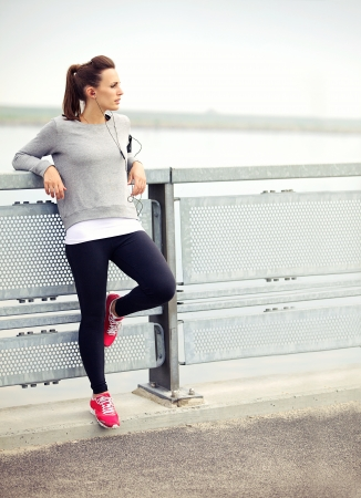 Female jogger resting while listening to mp3 music