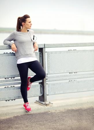 female jogger: Mujer descansando mientras escucha m�sica mp3 basculador