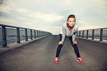 maraton: Enfocado corredor descanso al aire libre en el puente