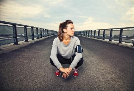 Corredor femenino que se sienta en el puente después de correr Foto de archivo