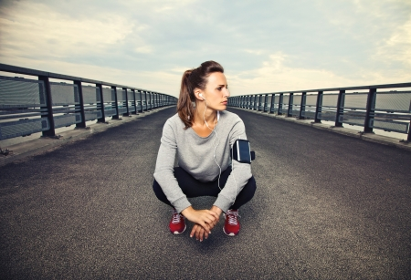 Female runner sitting on the bridge after running Banco de Imagens