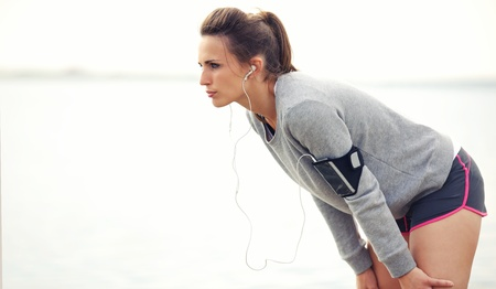 Focused female runner on a break after running workout photo