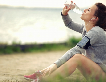 Female runner sitting on the grass while drinking water photo