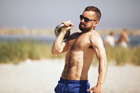 snatch: Man doing crossfit WOD on beach with a heavy kettlebell