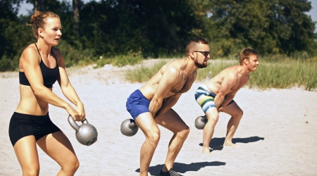 kettle bell: Group doing crossfit workout on beach on a hot summer day