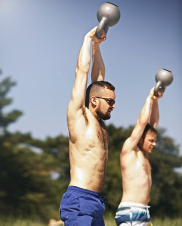 fit: Two strong young men lifting heavy kettlebell weights