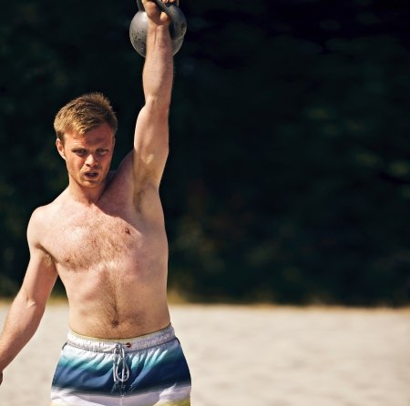 scandinavian people: Guy lifting a heavy kettlebell on a beach during crossfit workout. Copy space right.
