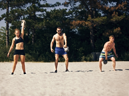 Three people doing crossfit workout on a beach photo