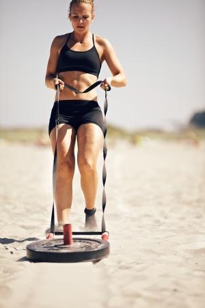 Crossfit 運動: 砂の上のそりを引っ張る