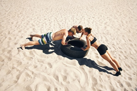 intense: A group of crossfitters doing push-ups on tire Stock Photo