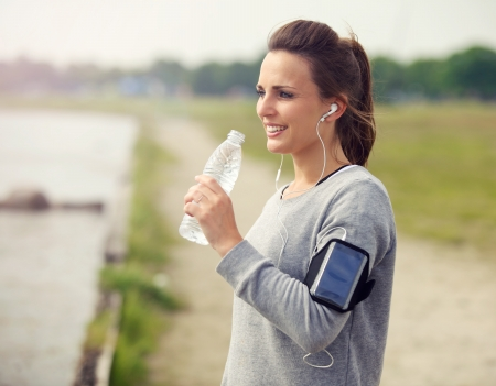 girl drinking: Female runner smiling while drinking bottled water