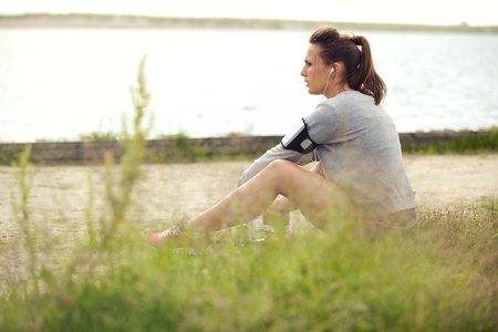 Tired female runner sitting on the grass having her break photo