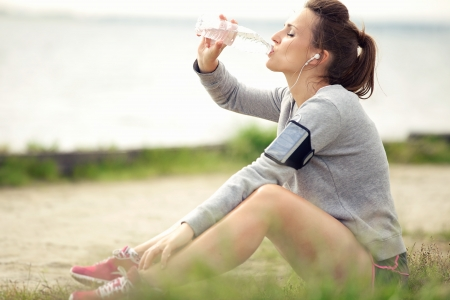 female jogger: Corredora cansado que se sienta en la hierba y el agua potable embotellada Foto de archivo