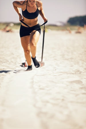 Female crossfitter pulling a sled on sand during crossfit workout photo