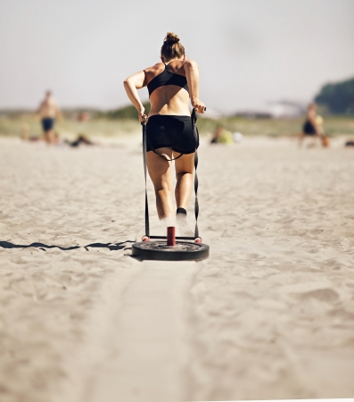 Woman Pulling Crossfit Sled Stock Photo - 21580583