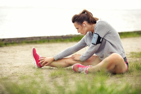 Woman in sportswear outdoors stretching her legs before running Reklamní fotografie