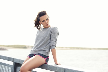 Confident female runner sitting and resting outdoors after workout Stock Photo - 21777999