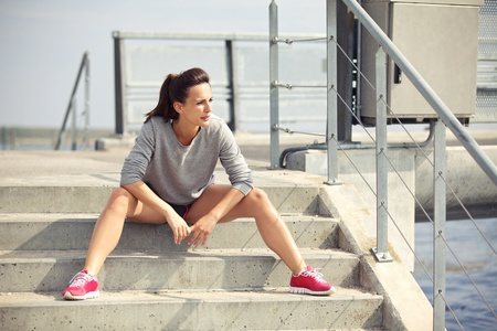 Female athlete sitting on the stairs taking a break from running photo