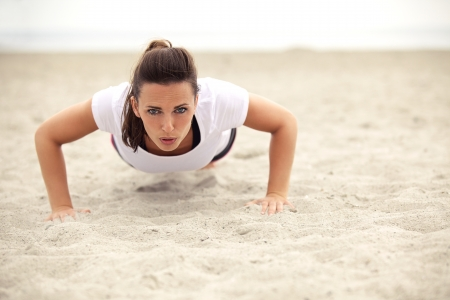 Fitness sports woman on the beach doing push up exercise while looking in camera. Beautiful young athletic european model in her 20s.
