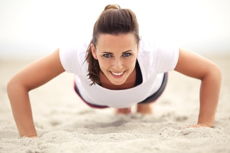 lifestyle outdoors: Happy fitness caucasian woman on the beach smiling while doing push up exercise. Active and healthy lifestyle.