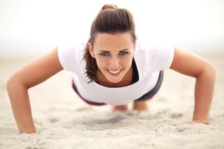 lifestyle: Szczęśliwa kobieta fitness kaukaski na plaży uśmiecha się robi push up ćwiczenia. Aktywny i zdrowy tryb życia.