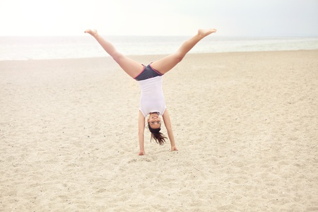 Cheerful outdoor woman on the beach doing a handstand photo