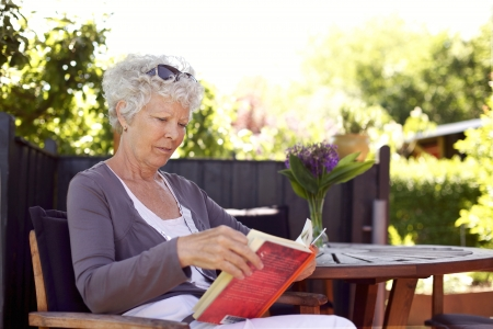 Relaxed senior woman sitting a chair in backyard garden reading a book photo