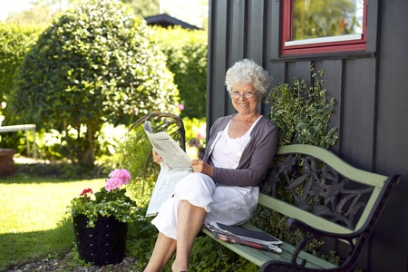 grannies: Relaxed elder woman sitting on a bench in backyard garden reading a newspaper looking at camera and smiling
