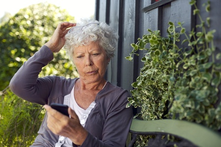 Elder woman sitting on a bench in her backyard reading text message on her mobile phone