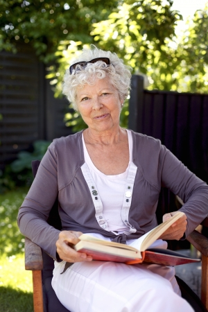 Happy mature woman sitting on a chair in garden with a book looking at camera smiling Stock Photo - 22106268