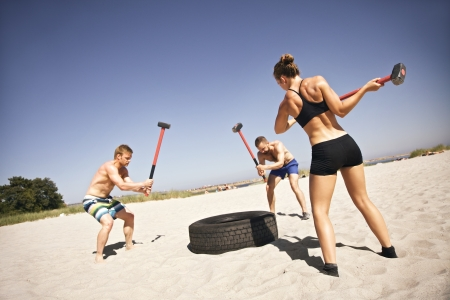 Three strong athletes doing hammer strike on a truck tire during crossfit exercise outside on beach