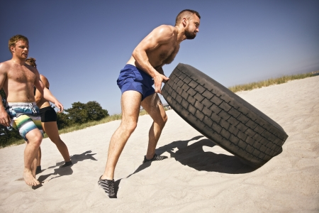 crossfit: Tough male athlete flipping a truck tire. Young people doing crossfit exercise on beach.
