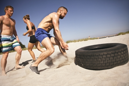 Strong male athlete about to flip a truck tire