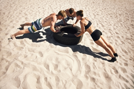 Small group of people doing push-ups on tire