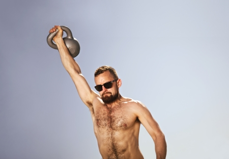 Male athlete swinging a kettle bell over his head with one hand photo