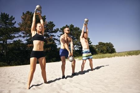Groep atleten swingende een ketel bel boven hun hoofd op het strand
