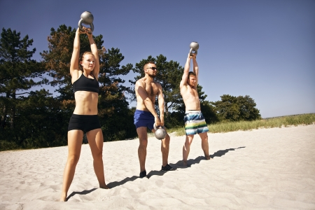 Group of athletes swinging a kettle bell over their head on beach Stock Photo