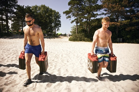 strong toughness: Two tough young male crossfitters lifting heavy jerrycans and walking during a crossfit workout on the beach. Stock Photo