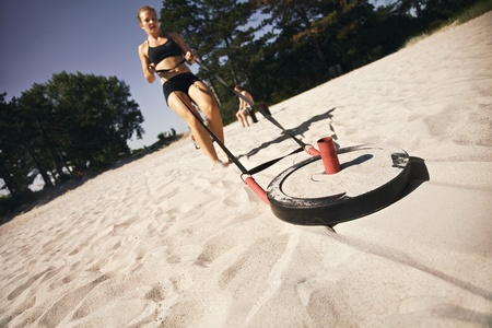 Strong young woman pulling a crossfit sled across a sandy beach outdoors on a hot summer day