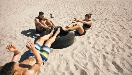 abs: Three young athletes doing abdominal exercise with a truck tire on beach. Athletes doing crossfit workout outdoors