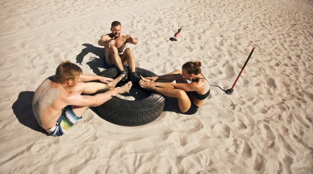 team effort: Small group of young athletes doing abdominal exercise with a truck tire on beach Stock Photo