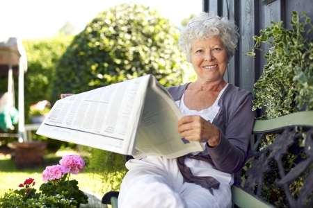 Relaxed senior woman sitting on a bench in backyard garden reading a newspaper looking at camera and smiling