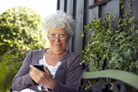 Senior woman using a mobile phone while sitting on bench in her backyard garden Stock Photo
